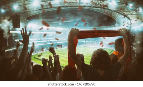 Football scene at night match with with cheering fans at the stadium