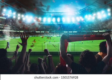 Football scene at night match with cheering fans at the stadium
