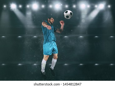 Football scene at night match with player jumping to hit the ball with head