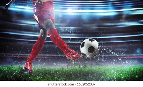 Football scene at night match with player in a red uniform kicking the ball with power