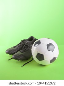 Football shoes and Soccer Ball against on green background,Copy space.