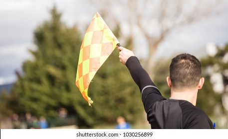 Football soccer arbiter assistant observes the match and raises the flag with his hand. Blurred blue sky, nature, players background, close up view, details.