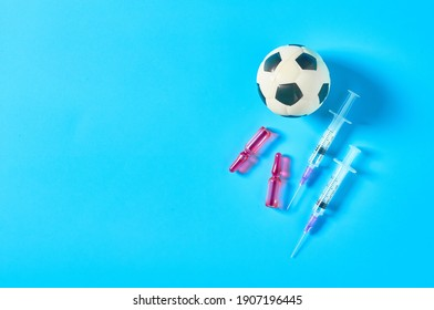 Football, soccer ball near syringe and ampoule on blue background. Concept of doping in professional sport. Rehabilitation, treatment after competition. Illegal medicaments using on tournament