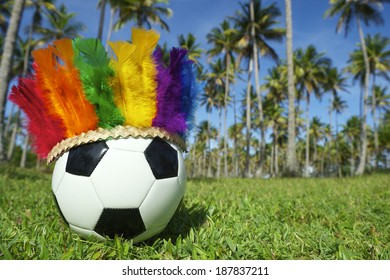 Football soccer ball wearing bright Brazilian carnival headdress in rainbow colors near grove of palm trees