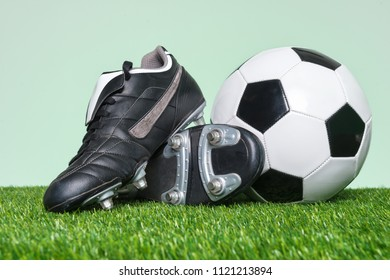 Football or Soccer boots and ball on grass with green background.