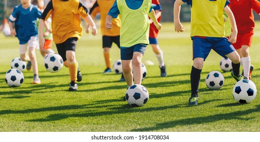 Football soccer children training class. Kids practicing football on grass field. Group of school children running and kicking soccer balls on summer training camp