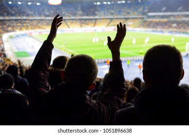 Football- soccer fans support their team and celebrate goal in full stadium with open air with nice sky.-blur picture.