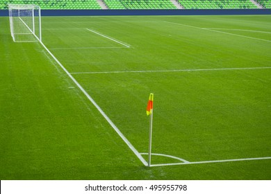 Football soccer field with white marks, green grass texture and corner flag.