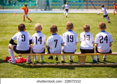 Football soccer match for children. Kids waiting on a bench.