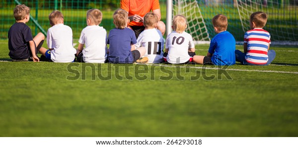 Football soccer match for children. Kids waiting on the game. briefing with trainer