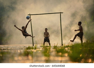 Football, soccer match. A player shooting on goal. Childen playing football.