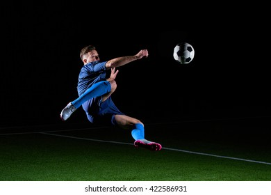 Football or soccer player with ball in action outdoors