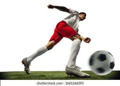 Football or soccer player on white background with grass. Young male sportive model training. Attacking, catching. Concept of sport, competition, winning, action, motion, overcoming. Wide angle.