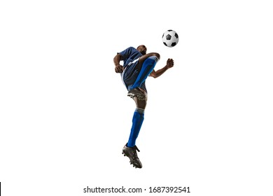 Football or soccer player on white background with grass. Young male sportive model training, practicing. Attacking, catching. Concept of sport, competition, winning, motion, overcoming. Wide angle.