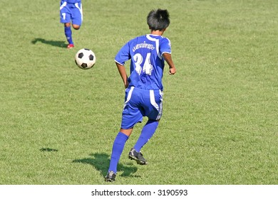 Football (soccer) player passes the ball