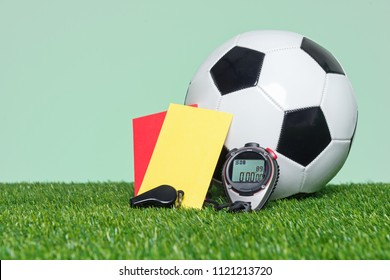 Football or Soccer Referee equipmnt and ball on grass with green background.