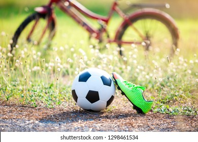 football and soccer shoes with blurry of red bicycle and green grass for outdoor sport