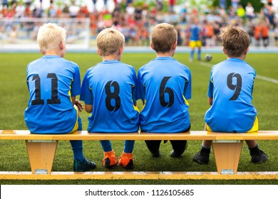 Football soccer tournament match for children. Kids substitute players sitting on a wooden bench. Football school competition for young boys