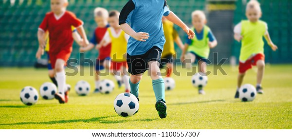 Football soccer training for kids. Children football training session. Kids running and kicking soccer balls. Young boys improving soccer skills