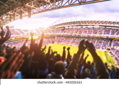 Football- Soccer,a lot of fans  in full stadium celebrate there goal in  open air roof stadium in summer. -blurred technique.