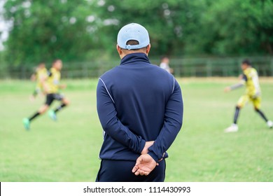 Football or socker coach observing kid football match.Healthy sport concept.
