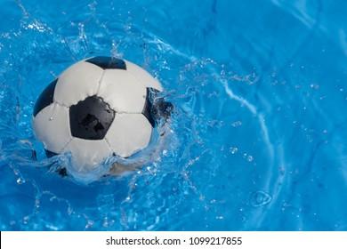 Football splashing in water