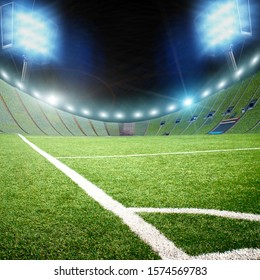 Football stadium and a corner of a field with green grass and bright lights with flashes