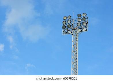 a football stadium floodlight , blue sky