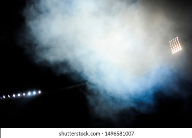 Football stadium floodlights are seen through dense fog