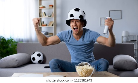 Football supporter in fan hat sincerely rejoicing to scored kick at last minutes