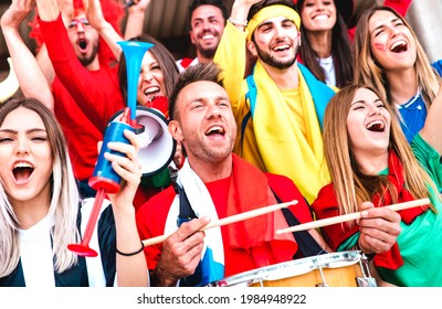 Football supporter fans cheering with drums watching soccer cup match at stadium bleachers - Young people group with multicolored t-shirt having excited fun on sport championship - Bright vivid filter
