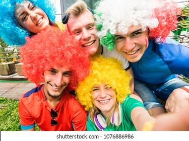 Football supporter fans friends taking selfie after soccer cup match hanging around together - Young people group with multicolored t-shirts and wigs having excited fun on sport world championship