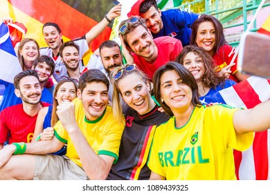 Football supporter taking a selfie at stadium. Friends cheering and watching soccer match together at stadium. International and multiracial group with multicolored t-shirts having fun.