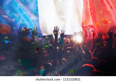 football supporters with raised hands against France flag - crowd in stadium celebrating victory