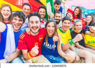 Football supporters together at stadium during a match. Friends cheering and watching soccer match together at stadium. International and multiracial group with multicolored t-shirts having fun.