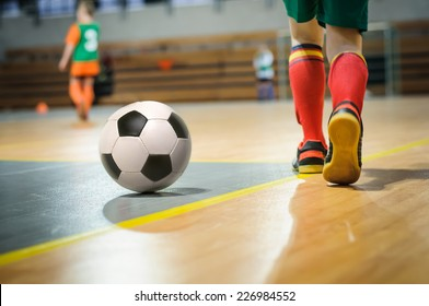 Football training for children. Indoor soccer young player with a soccer ball in a sports hall. Sport background.
