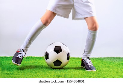 Football training for children. Soccer training dribbling. Indoor soccer young player with soccer ball in artificial grass studio. Player in white uniform. Grey background.