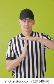 Football umpire against green background hand gesturing a time out