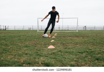 Footballer doing cone dribbling drill on field. Footballer moving the ball in between the cones practicing dribbling.