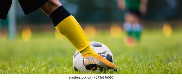 Footballer Kicking Ball Moment. Closeup of Soccer Players Leg Moving Toward Soccer Ball. Athlete in Soccer Cleats Running and Kicking Ball on Grass Turf Field