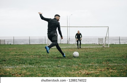 Footballer kicking a penalty shot. Soccer player kicking the ball towards the goal post with the goalkeeper in position.