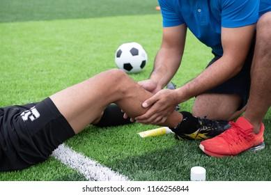 Fußballer mit blauem Hemd, schwarze Hose verletzt im Rasen während des Rennens.
