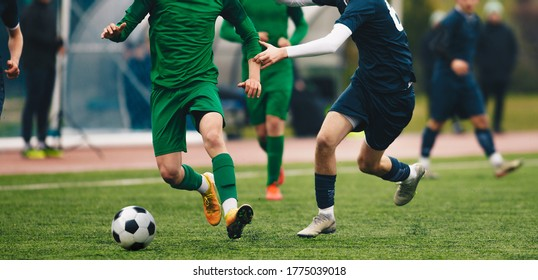 Footballers in action on the tournament game. Soccer football players competing for ball and kick ball during match in the stadium. Adult football competition