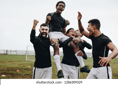 Footballers shouting in joy and pumping their fists after a win. Players walking on field carrying a teammate on shoulders celebrating a win.