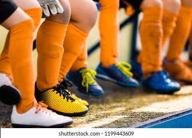 Footballers in soccer cleats. Youth athletes in soccer clothes. Young football players wearing football clothes and soccer shoes sitting on bench in a row. Soccer detail background.