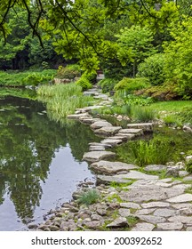 Footbridge across the pond made of stones. This element of  japanese garden is called ishibashi.