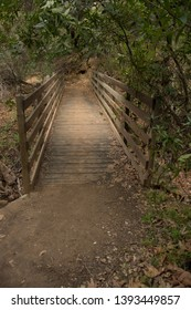 Footbridge in the beautiful Topanga Canyon, California.  Wooden foot bridge crossing dry creek bed in a canyon.  Dirt path, grey earth and old wood.