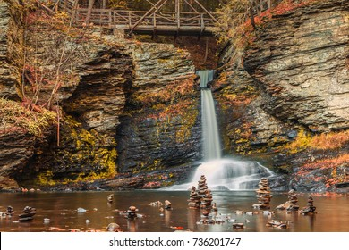 A footbridge and cairns surround Deer Leap Falls in peak fall foliage at  Delaware Water Gap in Pocono Mountains, PA