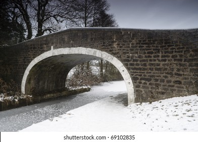 A footbridge crosses an icy canal during the winter.