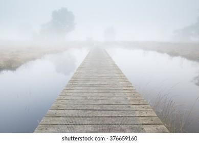 Footbridge ends in a foggy landscape